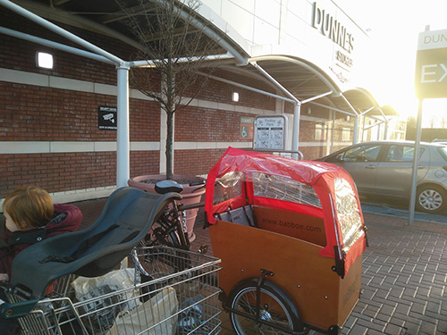 Shopping trolley with groceries beside cargo bike at Dunnes Stores, Dublin, Ireland