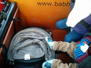 Buggy folded up beside children in Babboe Big cargo bicycle