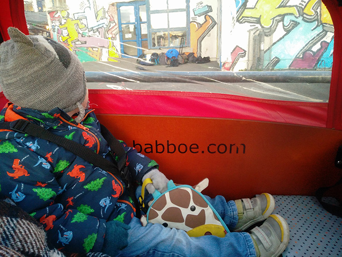 Child relaxing in a Babboe Big cargo bike